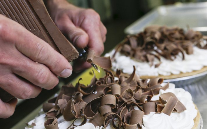 Bill McCauley puts chocolate shavings on a chocolate cream pie at Kathy's Pies, 616 5th Ave SE, in southeast Cedar Rapids on Tuesday, April 19, 2016. (Jim Slosiarek/The Gazette)