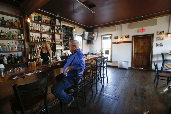 "Hopi James, who co-owns The Cider House in Fairfield, talks with a customer on Wednesday, Feb. 22, 2017. The pub serves its homemade cider plus other local and international beers and spirits, along with the 2015 ""Best Burger in Iowa."" (Rebecca F. Miller/The Gazette)"