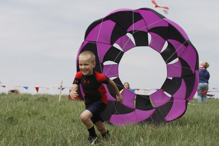 Eli Farmer, 7, competes in a parachute race during the Kites Over Hoover Park festival in West Branch on Saturday, April 23, 2016. (Tork Mason/Freelance)