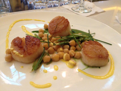 Pan Seared Scallops are served with salsa verde, cecci beans, grilled asparagus and preserved lemon emulsion.