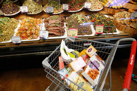 A shopping cart full of food sits by the deli counter at Lucky's Market in Iowa City on Wednesday, July 1, 2015. (Adam Wesley/The Gazette)