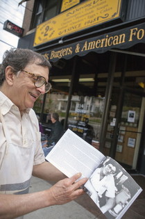 Former Hamburg Inn cook Gary Sanders shows off a portrait of himself in a newly published book in front of the eatery. (Justin Torner/Freelance)