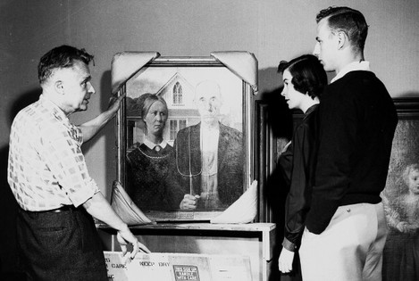 "The last time ""American Gothic"" was in Cedar Rapids before the current exhibit was in May 1952, when it was on display during the Coe College Centennial Fine Arts Festival. Prof. Marvin Cone (left) unpacks the painting as he talks with two students, Audrey Reggentin (center) and Wally Warner. Cone and Grant Wood became friends when both attended Washington High School in Cedar Rapids."